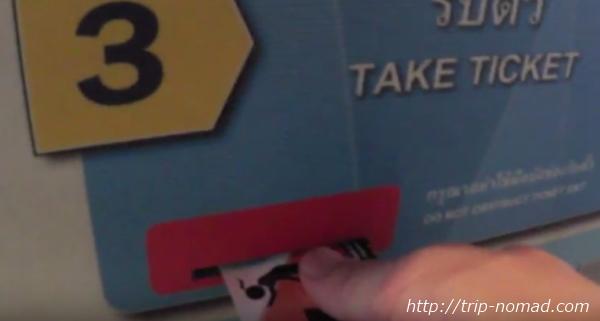 バンコク『BTS』券売機から出てきた切符を抜き取る